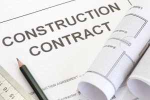 Close - up construction contract with pen and architectural roll